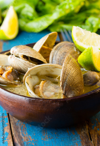 Seafood soup of clams in clay bowl on wooden blue background Poster