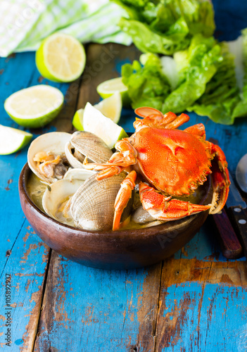 Seafood soup of clams decorated with crab in clay bowl on wooden blue background Canvas Print