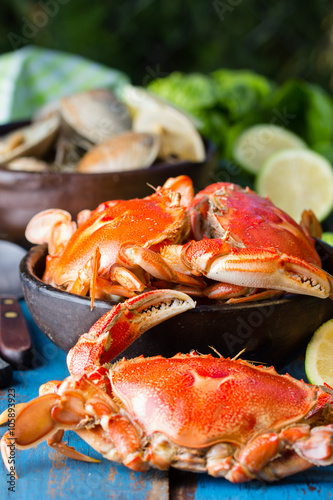 Fotobehang Schaaldieren Seafood. Bowl of crabs and soup of slams on wooden blue background. Traditional food on Holy week Easter in Latin America.