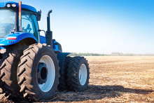 Blue Tractor On The Background Of An Empty Field