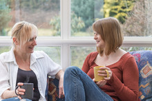 Middle Aged Woman And A Young Woman Are Chatting Together Sitting On The Sofa In The Conservatory.