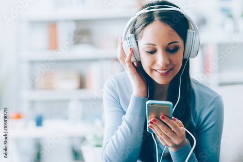 Girl listening to music with her smartphone Canvas Print