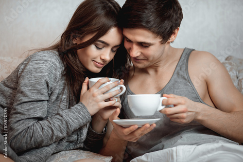 Fotografia  Young beautiful pair of lovers drink tea (coffee) in bed