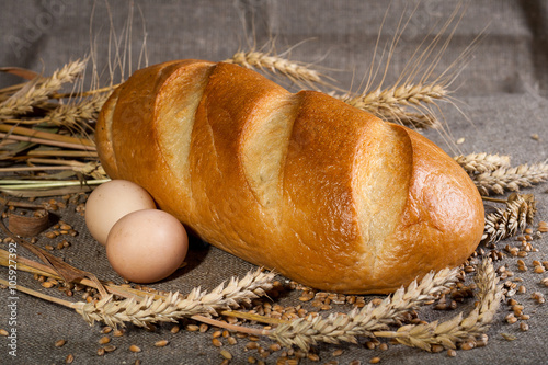obraz lub plakat Батон с яйцами и колосьями пшеницы