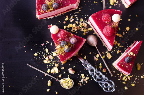 Pieces of delicious raspberry cake with fresh strawberries, raspberries, blueberry, currants and pistachios on black background. Free space for your text.