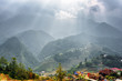 Scenic view of rays of sunlight through clouds at mountains