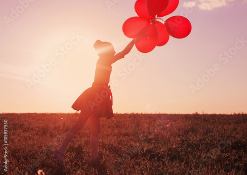 Photo  happy girl with red balloons outdoor