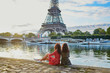 Beautiful twin sisters near the Eiffel tower in Paris, France