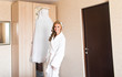 The bride in white bathrobe. Wedding preparations.