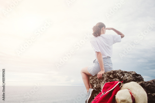 Young woman sitting on a cliff and looking far away at the sea