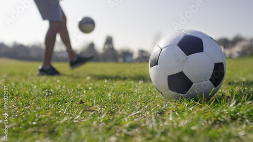 Football player doing kick ups in the park with a football in the foreground