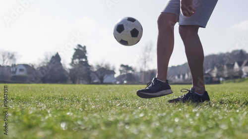 Football player doing kick ups in the park on a bright day