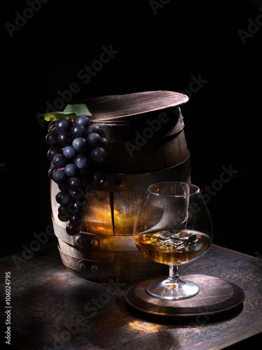 Oak barrels with grapes and brandy with ice
