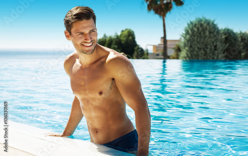 Fotomural Photo of handsome smiling man in swimming pool in summer scenery