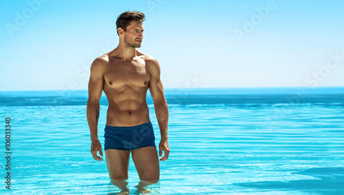 Fotografering  Panoramic photo of sexy man posing in swimming pool