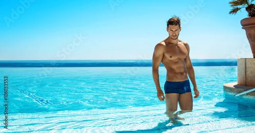 Cuadros en Lienzo  Muscular man in the swimming pool posing in summer scenery