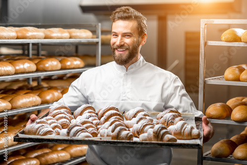 In de dag Brood Handsome baker in uniform holding tray full of freshly baked croissants at the manufacturing