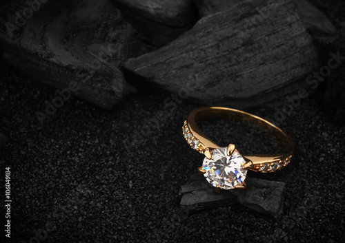 Photo  jewelry ring witht big diamond on dark coal and black sand backg