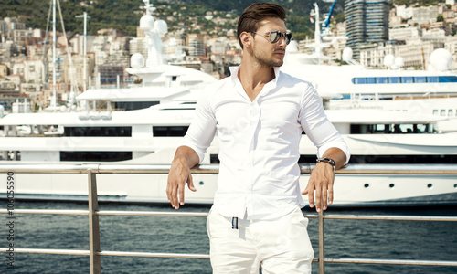 Fotomural  Photo of handsome man with luxury yacht in port
