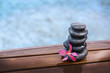 Stack of spa stones with pink orchid on wooden wet bridge