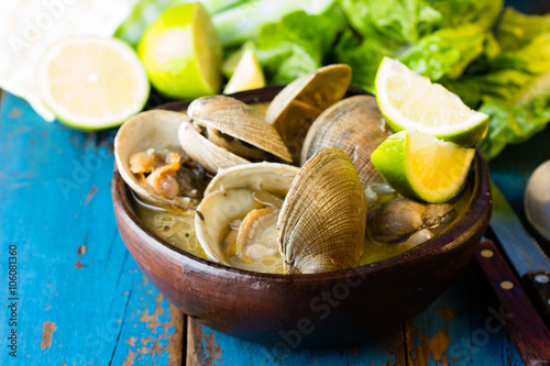 Seafood soup of clams in clay bowl on wooden blue background Canvas Print