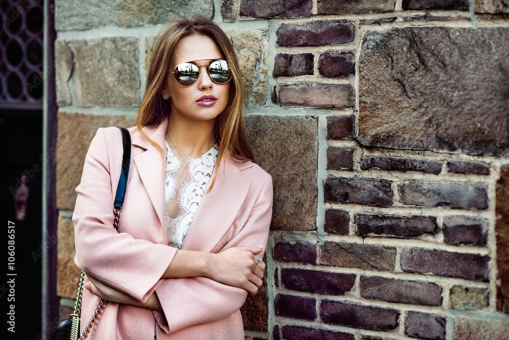 Fototapeta Beautiful fashion model woman wearing sunglasses and standing near brick wall