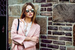 canvas print picture - Beautiful fashion model woman wearing sunglasses and standing near brick wall