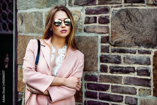 Obraz Beautiful fashion model woman wearing sunglasses and standing near brick wall - fototapety do salonu