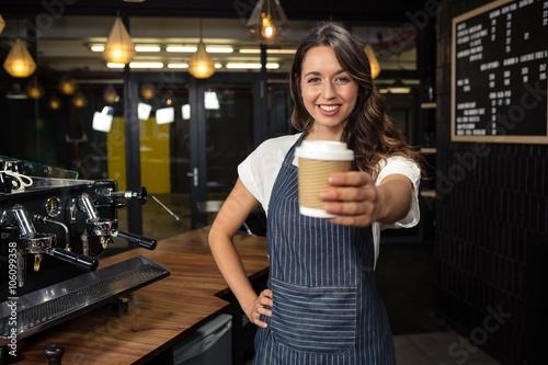 Fotografie, Obraz  Smiling barista holding disposable cup