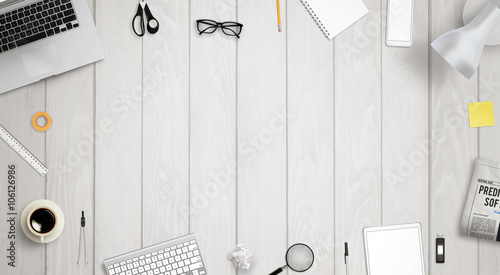 Work desk with free space for text surrounded with a lot of desk accessories. There is a laptop, tablet, phone, camera, headset, mouse, glasses, camera, pens, paper...