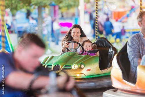 Poster Attraction parc Mother and daughter in bumper car at fun fair
