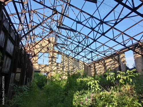 Staande foto Industrial geb. Abandoned industrial warehouse with missing roof, rusty beams - landscape color photo