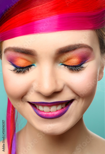 Fototapeta Beautiful girl with colorful makeup and hairstyle on blue background obraz na płótnie