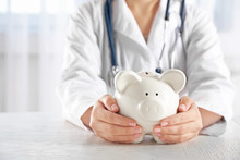 Doctor Hands With Piggy Bank C...
