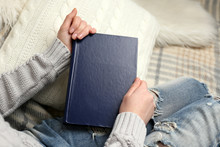 Young Woman Sitting On The Sofa With White Cushion And Holding A Blue Book Cover, Close Up