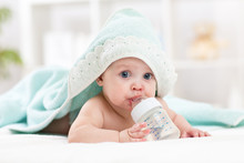 Happy Baby Girl Drinks Water From Bottle Wrapped Towel After Bath