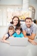 Portrait of smiling family with laptop on table