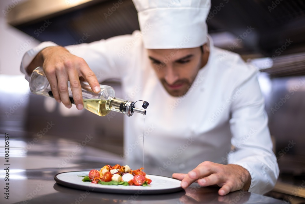 Fototapety, obrazy: Handsome chef pouring olive oil on meal