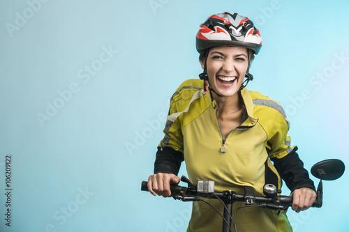 Fotografie, Obraz  Donna Ciclista con casco su sfondo celeste sorride in camera