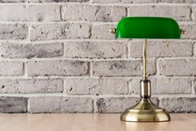 Green And Gold Banker Lamp On The Desk