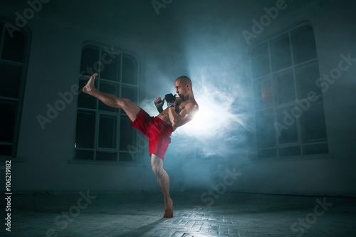 Photo The young man kickboxing in blue smoke