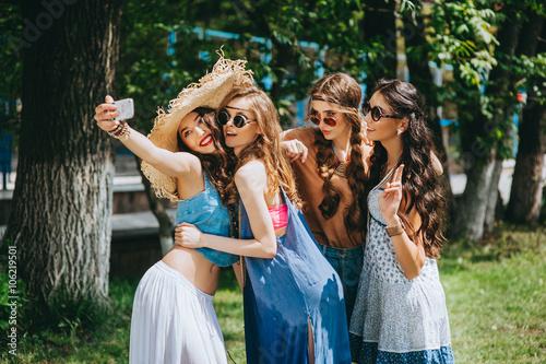 Photo  four beautiful girls hippies doing selfie outdoors