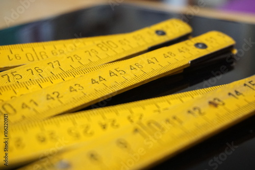 Old yellow folding meter ruler measuring centimeters on the