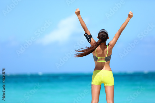 Fotografie, Obraz  Strong fitness athlete arms up in success on summer beach after cardio training workout