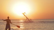 Silhouette of a Man Having Fun on Flyboard in the Sea at Sunset Background