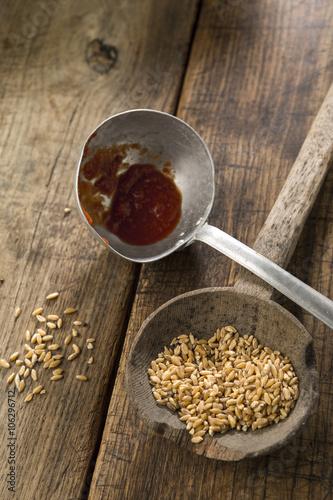 due mestoli da cucina con grano e sugo su un sfondo tavola ...
