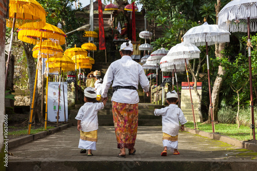 Poster Bali Man with children walks up the stairs during the celebration before Nyepi (Balinese Day of Silence). Ubud, Indonesia.