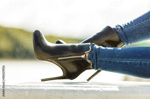 Fotografia  woman legs in denim pants heels shoes outdoor