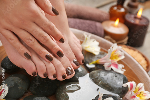 Foto op Plexiglas Manicured female feet and hand in spa wooden bowl with flowers and water closeup