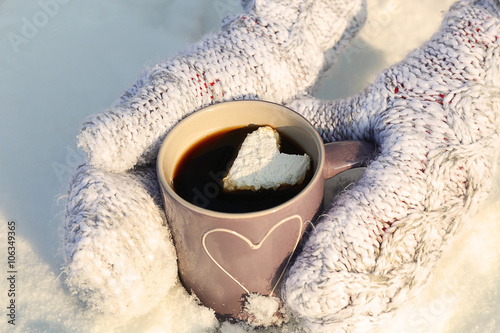 Canvas Prints Autumn Female hands in warm mittens holding cup of hot coffee with heart marshmallow on snowy background